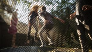 Pam King jumping on trampoline with children