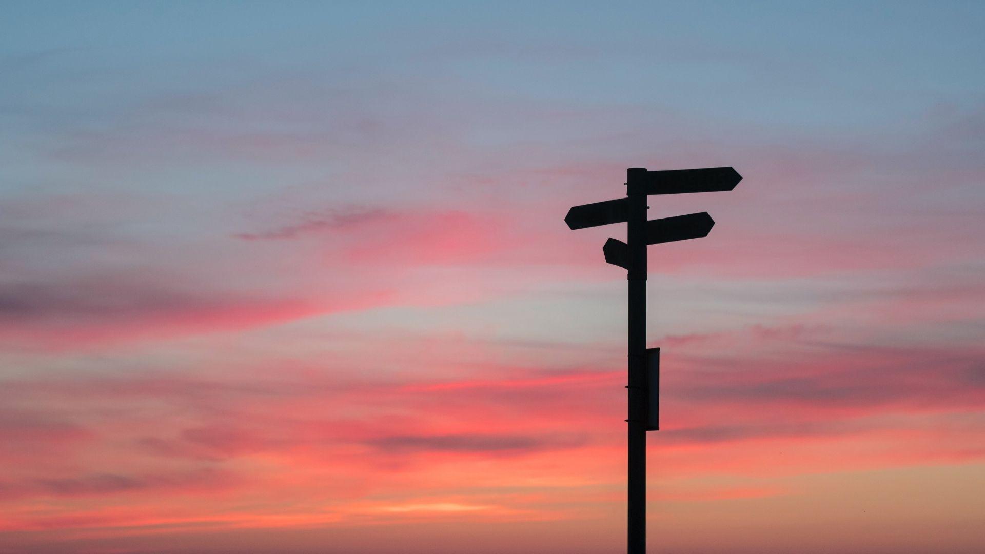 Sun setting on signposts