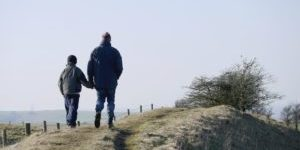 Father and son walking on road